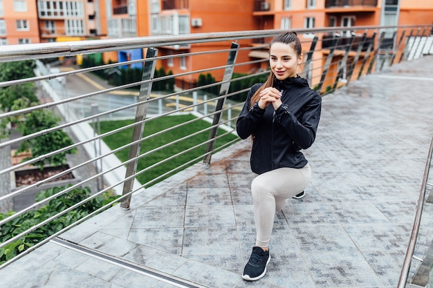 Morgens. junge, brunette trägt die frau zur schau, die beine auf der treppe in der modernen stadt ausdehnt. gesunder lebensstil in der großstadt.
