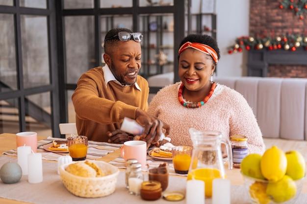 Morgens. positives freudiges paar, das am tisch sitzt, während sie zusammen frühstücken