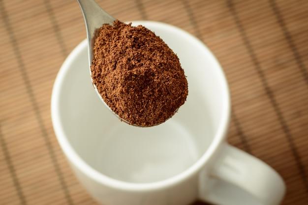 Morgens starken kaffee kochen. löffel mit kaffee in der nähe der weißen tasse