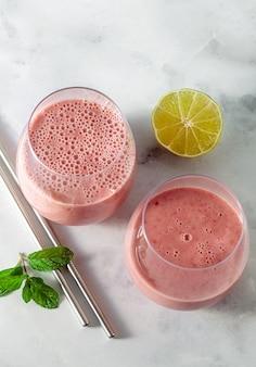 Morgens süßer frühstücks-smoothie aus hafermilch, banane und himbeeren mit limettensaft