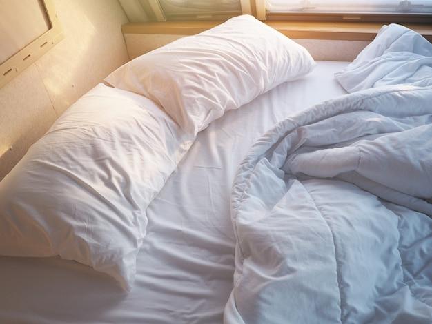 Morgens ungemachtes schlafzimmer. weißes kissen und decke mit falten unordentlich auf dem bett.