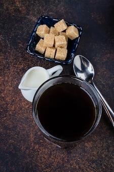 Morgenschale heißer kaffee mit milch und zucker auf dunkler konkreter hintergrundsteintabelle. ansicht von oben