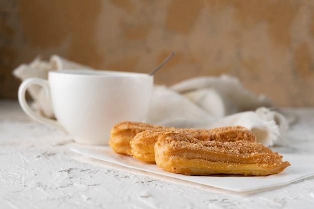 Morgensnack mit kaffee und sahnigem eclair auf einer tabelle mit weißer tischdecke, geschäftsfrühstück