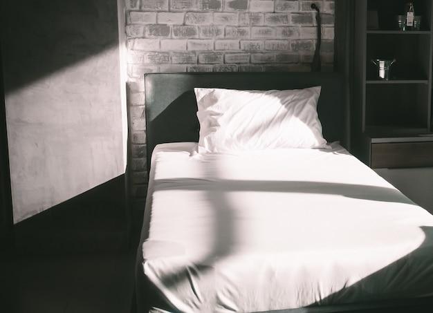 Morgensonne auf schlichtem weißem bettlaken im loft-stil