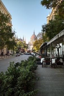 Morgenstadtstraßenlandschaft mit blick auf das ungarische paliament-gebäude auf einem klaren blauen himmelshintergrund im herbsttag, budapest, ungarn.