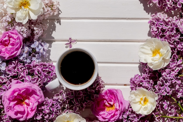 Morgentasse schwarzen kaffee und zweig der blühenden lila flieder mit grünen blättern auf weißem hintergrund. zusammensetzung mit weißer tasse kaffee, schöner fliederstrauß. konzept von frühling und komfort.