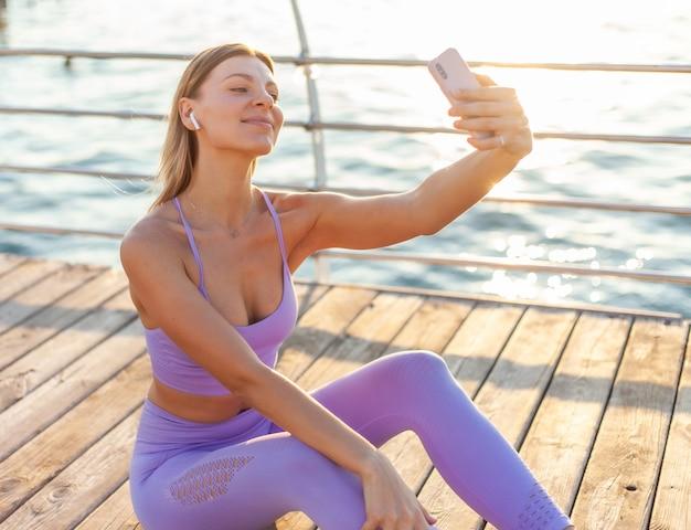 Morgentliches training. junge frau in sportbekleidung mit kopfhörern, die selbstporträt auf smartphone am strand bei sonnenaufgang tun