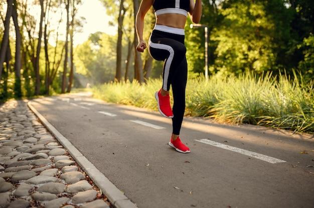 Morgentraining im park, frau, die auf gehweg läuft. die läuferin treibt an einem sonnigen tag sport