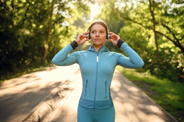 Morgentraining im park, frau in kopfhörern hört musik auf dem gehweg. die läuferin treibt an einem sonnigen tag sport