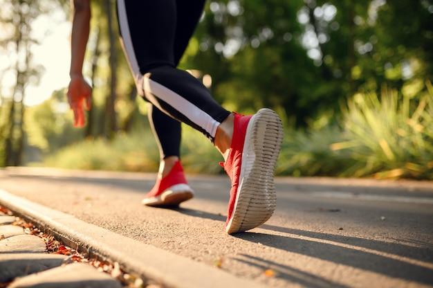 Morgentraining im park, frau in sportbekleidung auf gehweg. die läuferin treibt an einem sonnigen tag sport