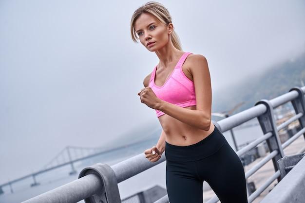 Morgentraining nahaufnahme rückansicht der jungen frau in sportkleidung beim joggen während des trainings