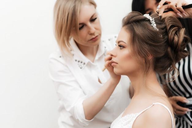 Morgenvorbereitungen für die hochzeit der braut in einem schönheitssalon. eine maskenbildnerin macht make-up und eine friseurin macht ihre haare