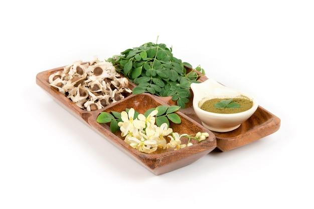 Moringa, grüne blätter, blumen, getrocknete samen und pulver lokalisiert auf weißem hintergrund.