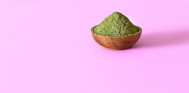 Moringa-pulver in der hölzernen schüssel auf rosa hintergrund