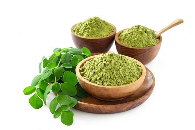 Moringa-pulver in der hölzernen schüssel mit den ursprünglichen frischen moringa-blättern lokalisiert auf weißem hintergrund.