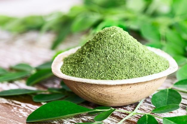 Moringa-pulver in einer schüssel mit frischen moringa-blättern