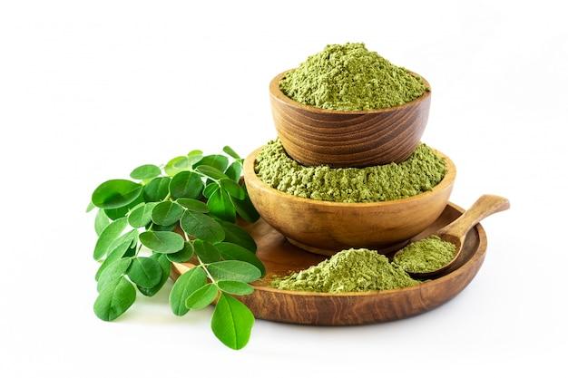 Moringa-pulver (moringa oleifera) in der hölzernen schüssel mit den ursprünglichen frischen moringa-blättern lokalisiert auf weißem hintergrund.