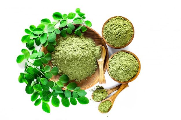 Moringa-pulver (moringa oleifera) in der hölzernen schüssel mit den ursprünglichen frischen moringa-blättern lokalisiert