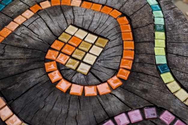 Mosaikfliesen auf rundem abgeholztem baum mit rissen stumpf außerhalb diy gartenmöbel von hand verziert kleine fliesen mosaik bunter schlangenpfad abstrakten natürlichen holzhintergrund