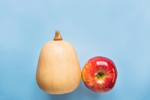 Moschuskürbis-kürbis reifes rotes apple auf blauem hintergrund. herbst herbst erntedankfest ernte