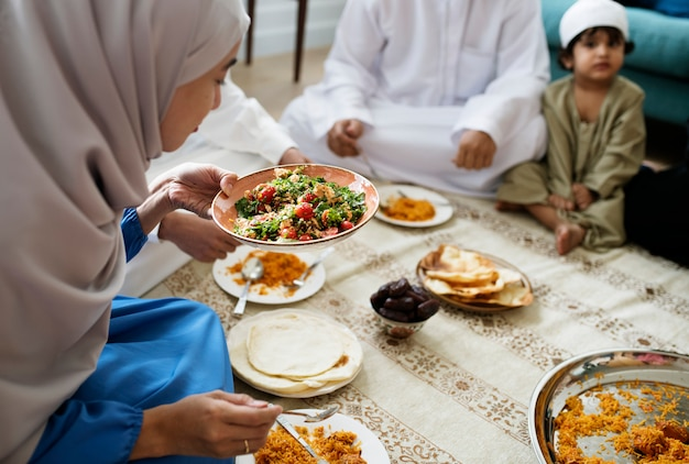 Moslemische familie, die auf dem boden zu abend isst