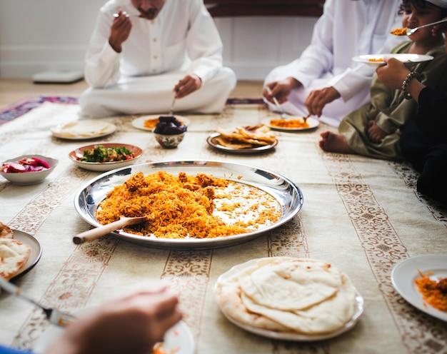 Moslemische familie, die auf dem fußboden zu abend isst