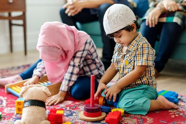 Moslemische familie, die sich zu hause entspannt und spielt