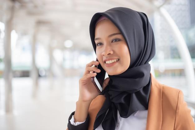 Moslemische frau des geschäfts, die telefon in der stadt verwendet.