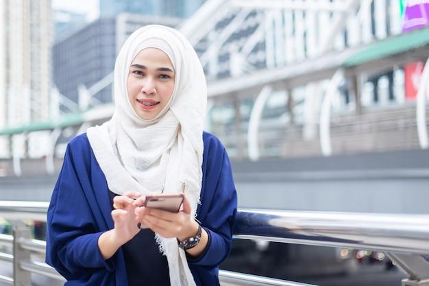 Moslemische frau des schönen jungen asiatischen geschäfts in einem tragenden hauptschal (hijab) uesing smartphone des anzugs