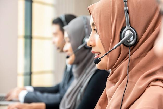 Moslemische frau, die als kundenbetreuungsbetreiber mit team in call-center arbeitet