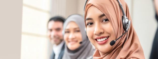 Moslemische frau, die als kundendienstbediener mit team in call-center arbeitet