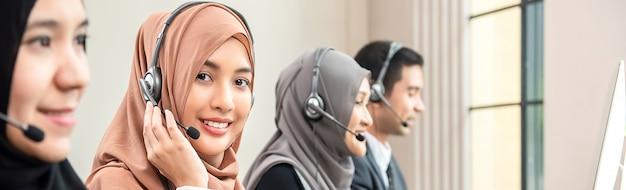 Moslemische frau, die als kundendienstbetreiber mit team im kundenkontaktcenter arbeitet