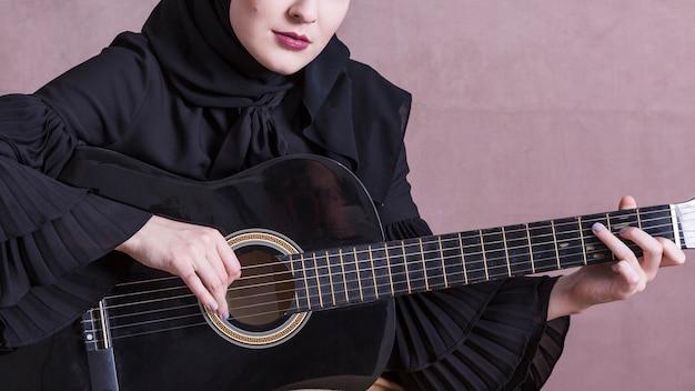 Moslemische frau, die auf der gitarre spielt