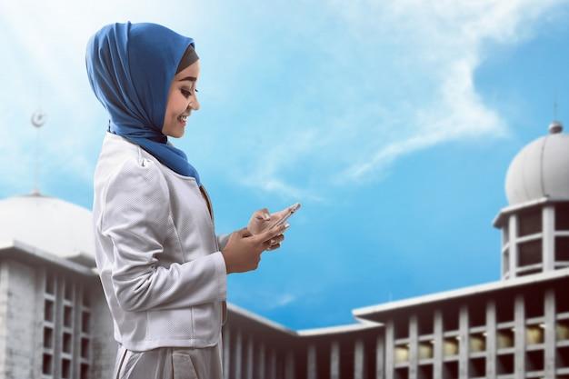 Moslemische frau, die auf mobiltelefon schreibt