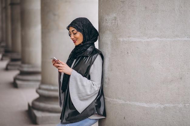 Moslemische frau, die draußen telefon in der straße verwendet
