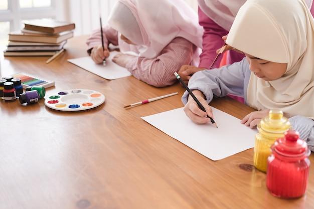 Moslemische frau, die ihre kinder zu hause malen und zeichnen unterrichtet.