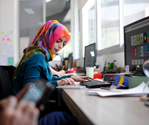 Moslemische frau, die im büro arbeitet