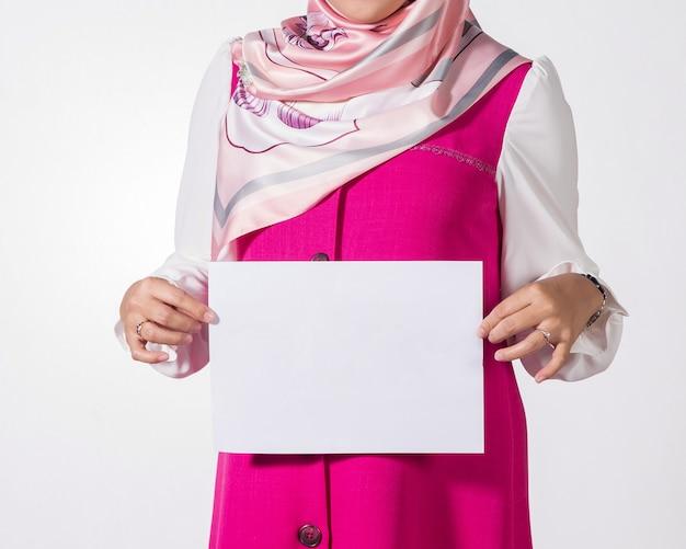Moslemische frau, die leeres weißbuch zeigt.