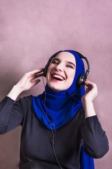 Moslemische frau, die musik auf kopfhörern hört