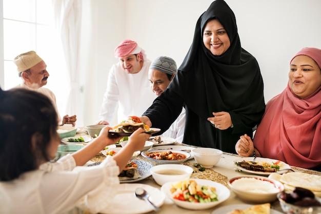 Moslemische frau, die nahrung am ramadan-fest teilt