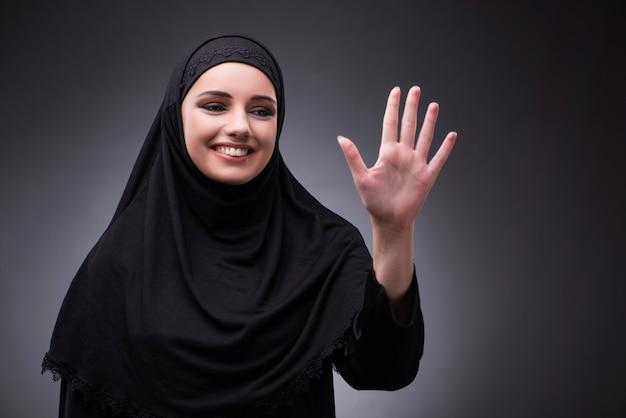 Moslemische frau im schwarzen kleid gegen dunklen hintergrund