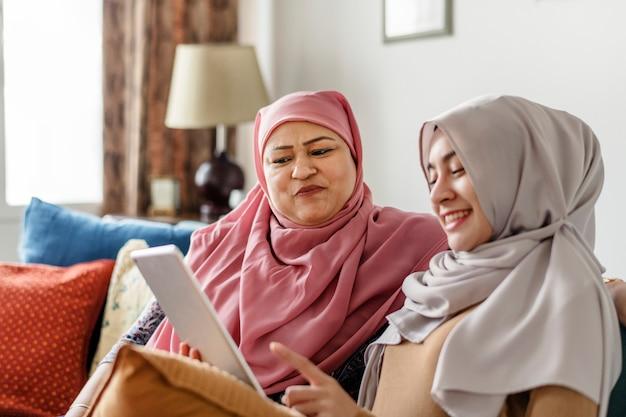 Moslemische frauen, die eine tablette verwenden