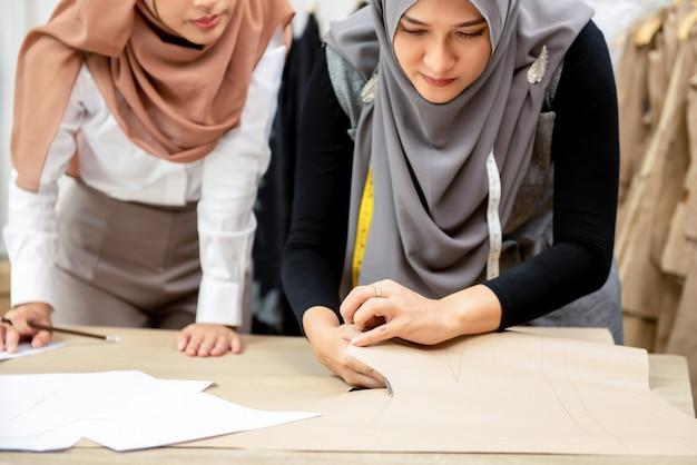 Moslemische frauenmodedesigner, die im schneidershop arbeiten