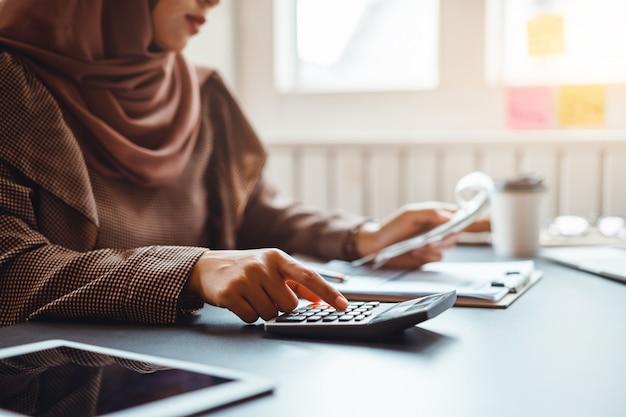 Moslemische geschäftsfrau, die ungefähr finanziell mit geschäftsbericht und taschenrechner im innenministerium arbeitet.