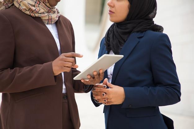 Moslemische geschäftsfrauen, die zusammen digitale tablette verwenden