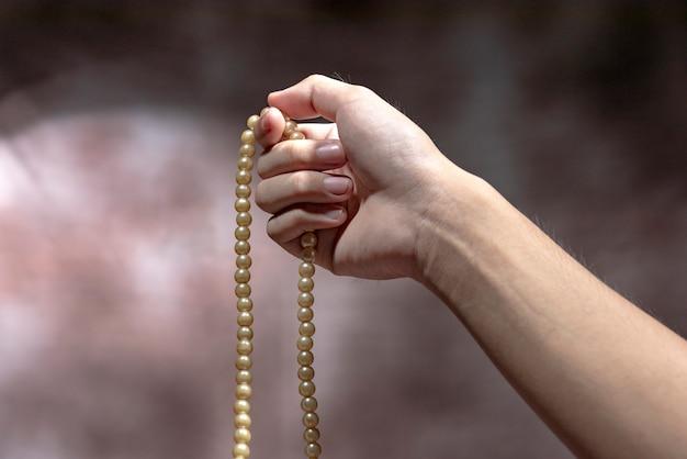 Moslemische hände, die mit gebetsperlen beten