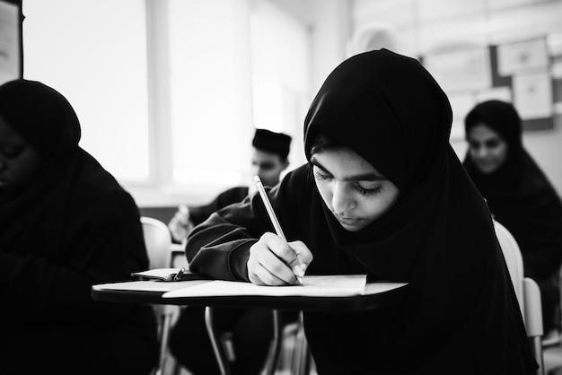 Moslemische kinder, die in einem klassenzimmer studieren