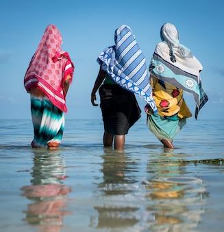 Moslemische mädchen im tropischen meerwasser