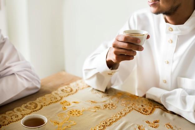 Moslemische männer, die eine tasse tee trinken