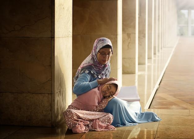 Moslemische mutter unterrichten ihre tochter, koran zu lesen